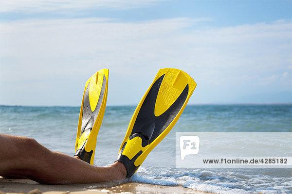 Mann mit Flossen am Strand