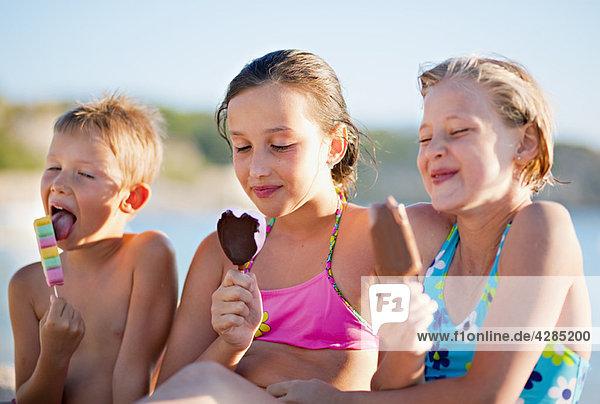 Kinder essen Eis am Strand Kinder essen Eis am Strand