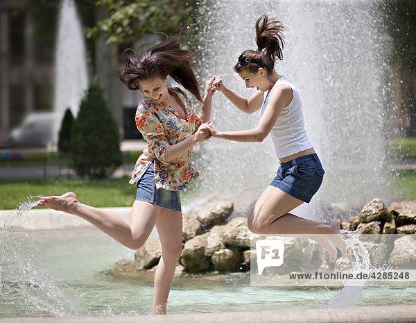 Junge Frauen beim Spritzen in einem Brunnen
