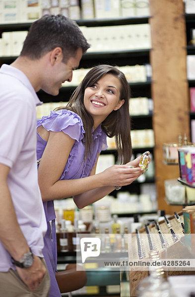 Junges Paar beim Einkaufen im Parfümeriegeschäft