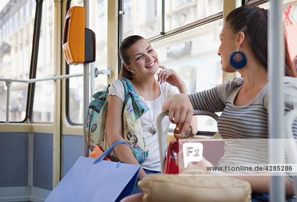 Junge Frauen sprechen in der Straßenbahn