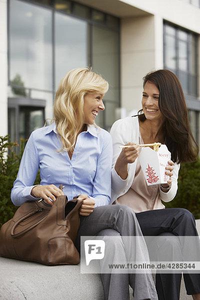 Zwei Geschäftsfrauen  die Essen mitnehmen.