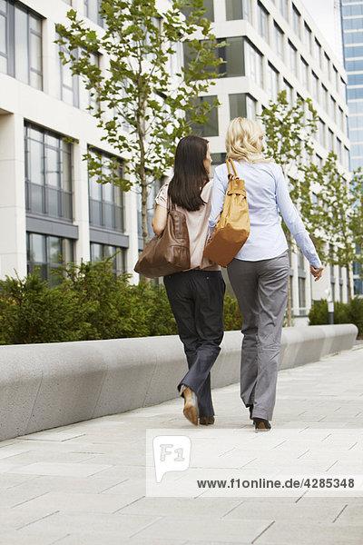 Two business women walking on sidewalk