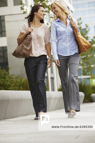 Geschäftsfrauen haben Spaß auf dem Bürgersteig