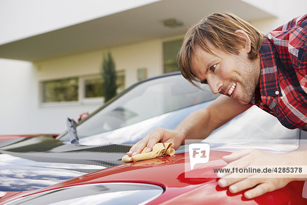 Mann poliert stolz Hi Elektroauto