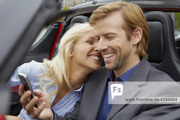 Paar in ihrem Elektro-Sportwagen  Fun