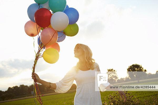 Mädchen mit Ballons draußen bei Sonnenuntergang