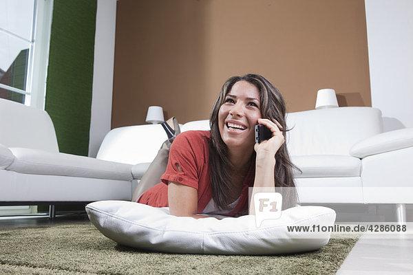 Junge Frau am Boden liegend mit Telefon