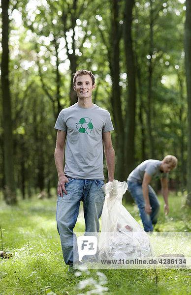 Junger Mann mit Müllsack in der Natur