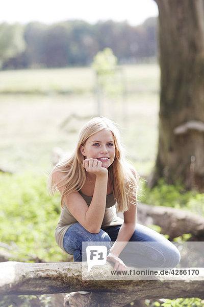 Junge Frau in der Natur sitzend