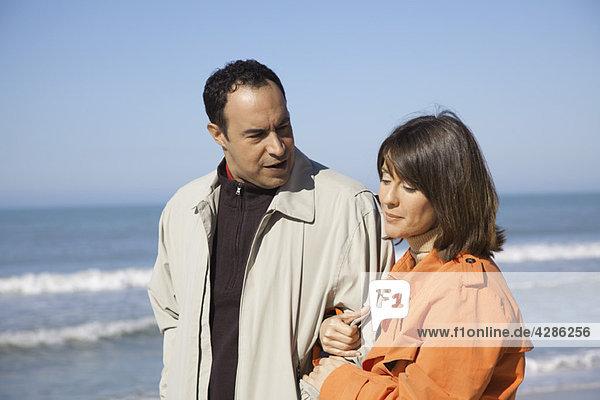 Reife Paare  die am Strand spazieren gehen und miteinander reden