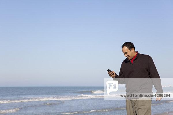 Mann sucht SMS auf dem Handy am Strand