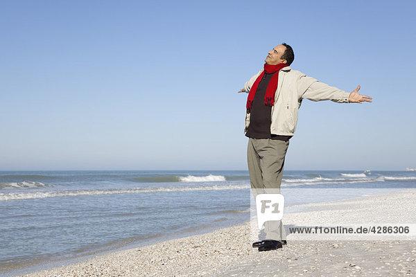 Mann steht am Strand mit ausgestreckten Armen und geht zurück.