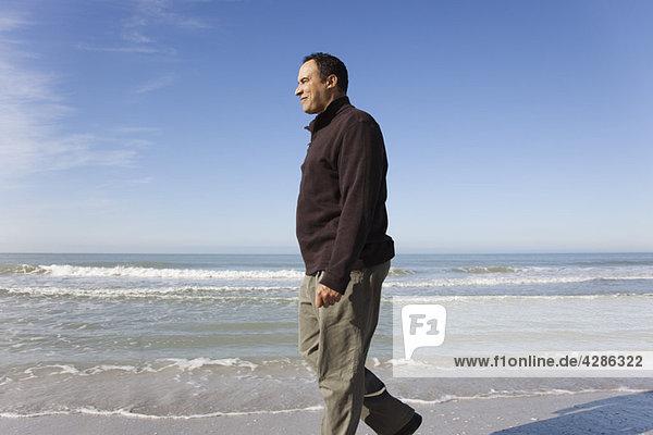 Erwachsener Mann  der am Strand spazieren geht