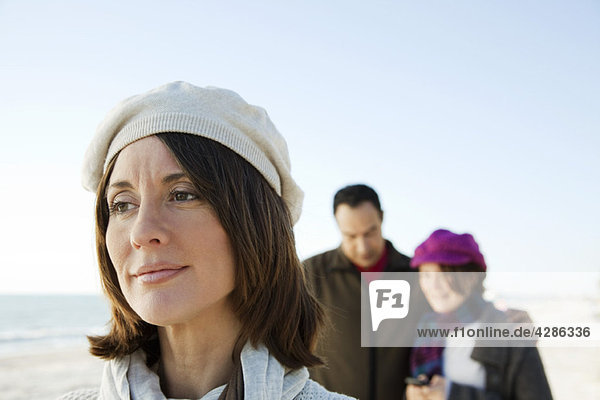 Frau schaut in Gedanken weg  Familie im Hintergrund
