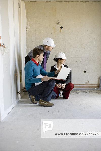Bauträger und Geschäftsleute mit Laptop auf der Baustelle