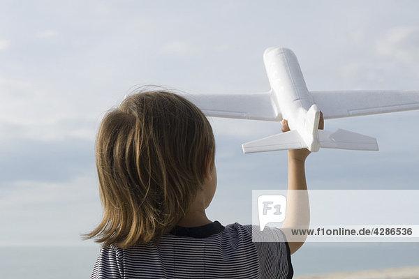 Kinder spielen mit Spielzeugflugzeug  Rückansicht