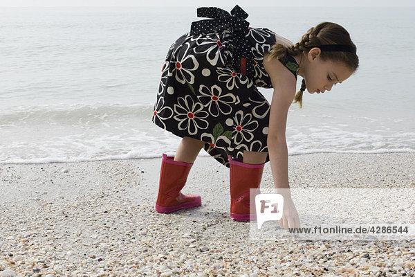 Mädchen beim Muschelsammeln am Strand