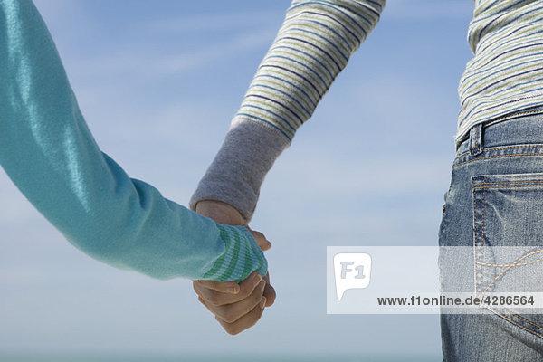 Elternteil mit Kinderhand  Rückansicht