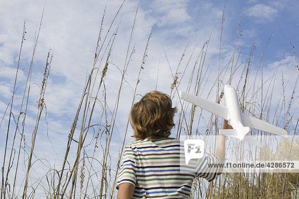 Junge spielt mit Spielzeugflugzeug