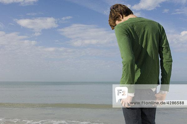 Junger Mann am Strand stehend mit Kopf nach unten  Rückansicht