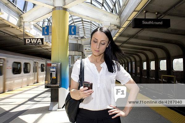Frau überprüfen ihr Telefon in u-Bahnstation  Toronto  Ontario  Kanada