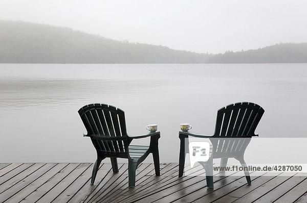 Liegestühle und Kaffeetassen auf Cottage dock an einem nebligen Morgen  Algonquin Park  Ontario