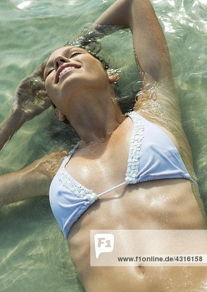 Junge Frau im Bikini im flachen Wasser am Strand liegend