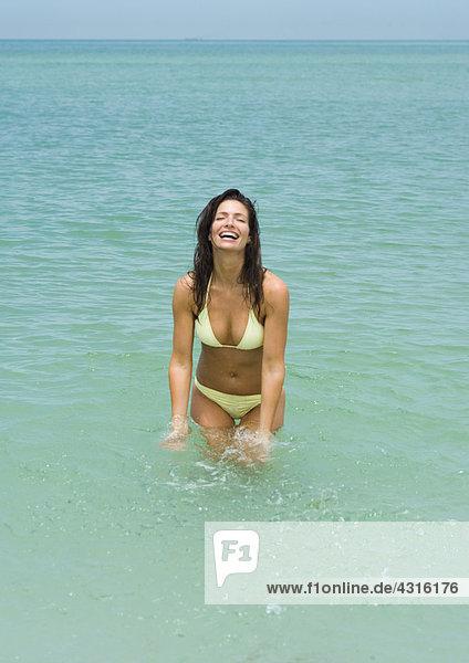 Frau im Meer stehend  lachend