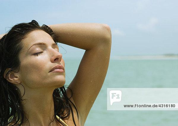 Frau mit geschlossenen Augen und Hand auf dem Kopf  Meer im Hintergrund