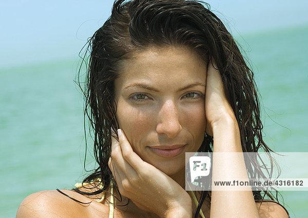 Frau mit Hand im nassen Haar  Meer im Hintergrund  Portrait