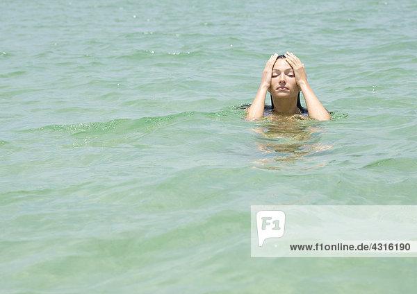 Frau im Meer  Hände auf dem Kopf