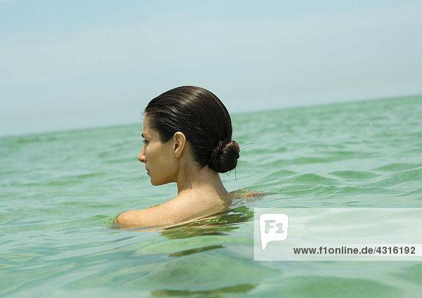 Frau mit nackten Schultern im Meer  Rückansicht