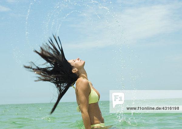 Frau  die im Meer steht und nasse Haare umdreht.
