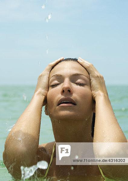 Frau im Meer  Hände auf Kopf und Augen geschlossen  Nahaufnahme