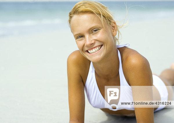 Frau am Strand liegend  lächelnd