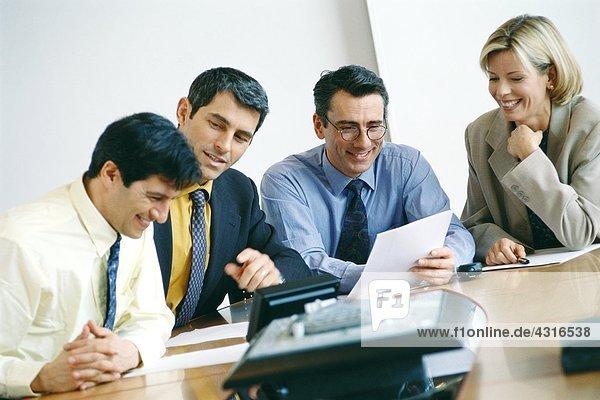 Geschäftskollegen sitzen im Meeting und lächeln