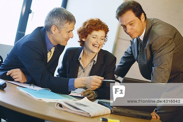 Business colleagues using laptop  laughing