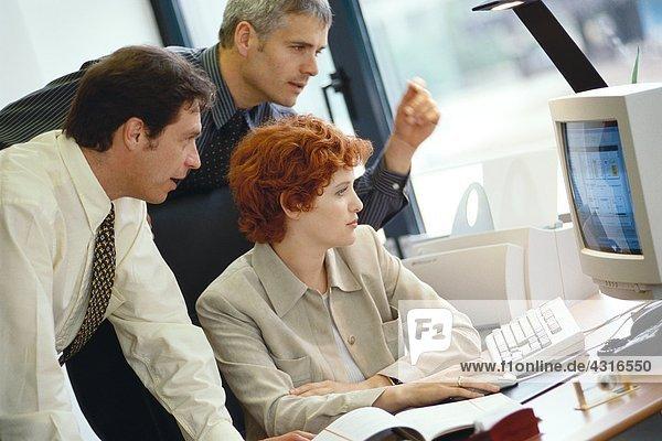 Geschäftskollegen  die gemeinsam am Desktop-Computer arbeiten