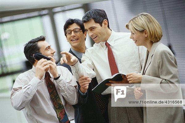 Vier Geschäftskollegen stehen in einer Gruppe  einer telefoniert  der andere hört zu.