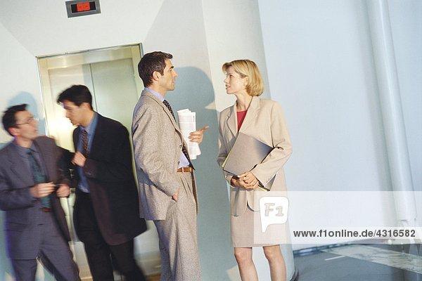Geschäftsfreunde im Gespräch mit dem Aufzug