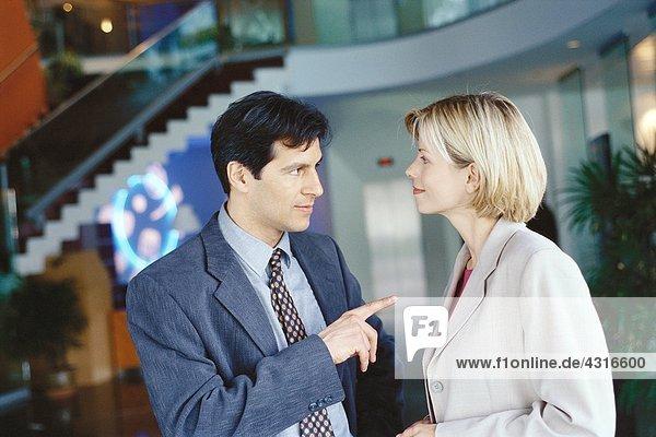 Männliche und weibliche Geschäftspartner stehen in der Lobby  Mann zeigt auf Frau