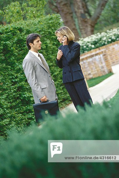 Male and female business associates standing outoors  woman using phone
