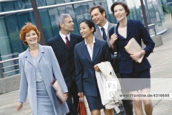 Gruppe von Führungskräften  die im Business Park spazieren gehen