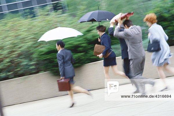 Gruppe von Führungskräften eilt durch den Regen