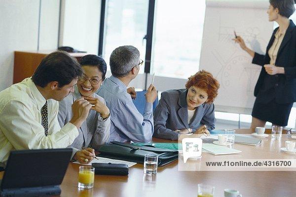 Kollegen am Tisch im Gespräch  lachend  bei der Geschäftspräsentation