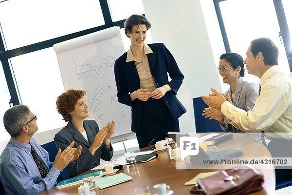 Kollegen klatschen für Geschäftsfrau nach der Präsentation