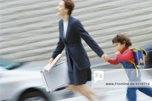 Geschäftsfrau  die sich beeilt und die Hand des kleinen Jungen hält.