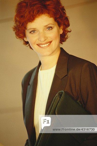 Geschäftsfrau stehend mit Aktentasche unterm Arm  Portrait