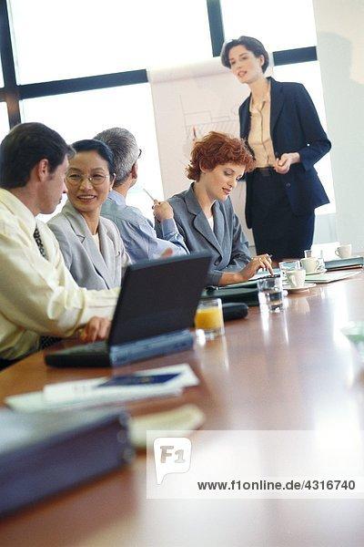 Gruppe von Geschäftsleuten am Konferenztisch während der Präsentation